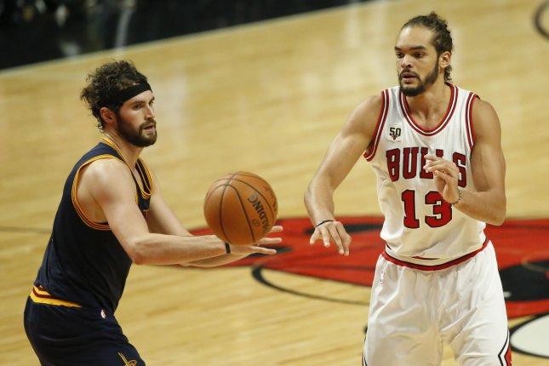 Chicago Bulls center Joakim Noah (R) passes the ball against Cleveland Cavaliers forward Kevin Love (L). Photo by Kamil Krzaczynski/UPI