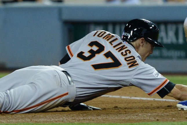 Kelby Tomlinson of the San Francisco Giants dives back to the base during a pickoff attempt. Photo by Jim Ruymen/UPI