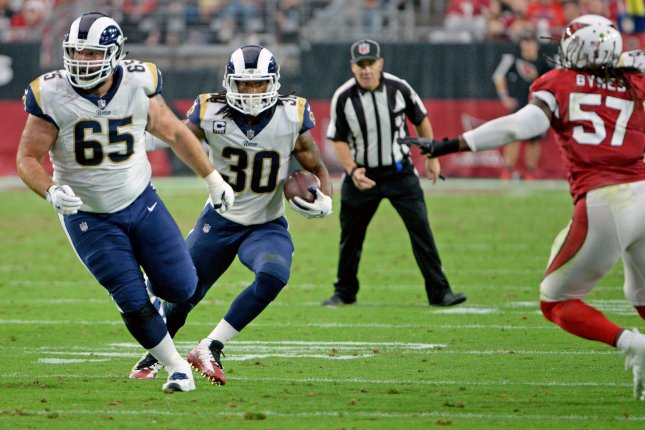 Los Angeles Rams' Todd Gurley II (C) follows his blocker John Sullivan for an eight yard pick-up in the second quarter against the Arizona Cardinals at University of Phoenix Stadium in Glendale, Arizona December 3, 2017. Hoping to make a play is Cardinals linebacker Josh Bynes (R). File photo by Art Foxall/UPI