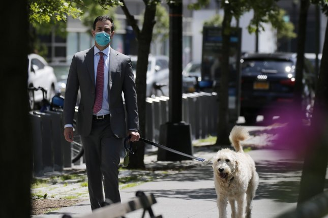 A man wears a protective face mask while walking a dog on a sidewalk on the Upper West Side of Manhattan in New York City in May. Photo by John Angelillo/UPI