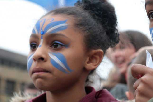 A young Yes campaigner watches the proceedings on the day Scottish residents decide the future political direction their country will take in Glasgow,Scotland on September 18, 2014.Ninety-seven percent of the population has registered to vote. EST. UPI/Hugo Philpott