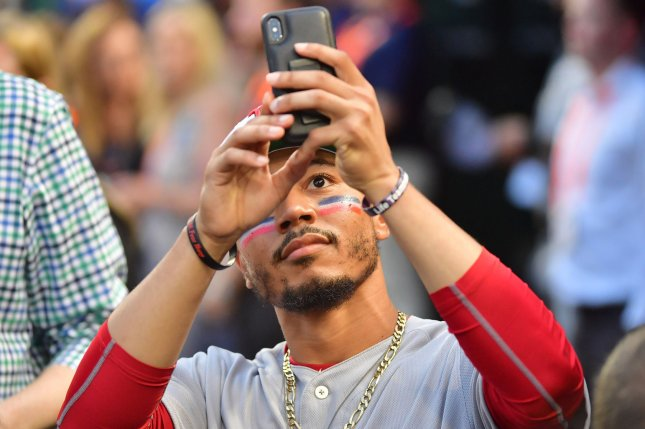 Boston Red Sox outfielder Mookie Betts (50) takes a photo of the crowd during MLB's All-Star Game on July 17 at Nationals Park in Washington, D.C. Photo by Kevin Dietsch/UPI