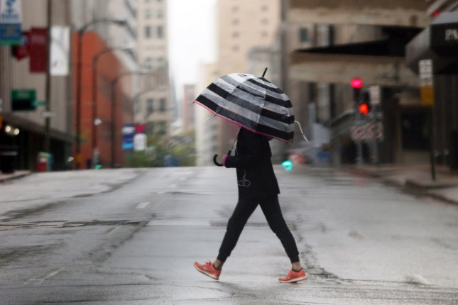 A woman carries an umbrella while crossing Pine Street in downtown St. Louis, Mo., on April 25. Forecasters say Mother's Day weekend will bring a chill in the East, heat in the West and rains in the Southeast. Photo by Bill Greenblatt/UPI