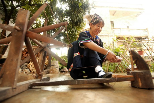 A woman is seen spinning a spool of cotton in China's Guangxi Province. Beijing's foreign ministry said Thursday the U.S. accusations have no merit. File Photo by Stephen Shaver/UPI