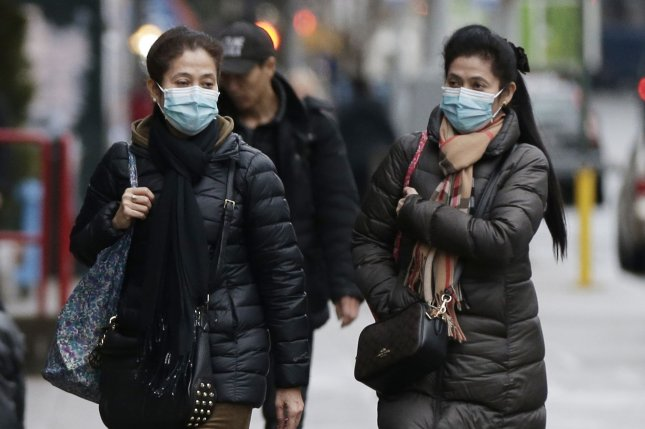 Two women wear face masks as they walk on the sidewalk in New York City's Chinatown on Thursday. Photo by John Angelillo/UPI