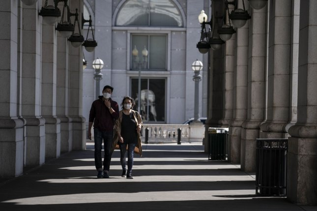 Masked pedestrians walk outside of Union Station in Washington, D.C., on October 6. The United States added another 58,400 COVID-19 cases on Monday. Photo by Sarah Silbiger/UPI