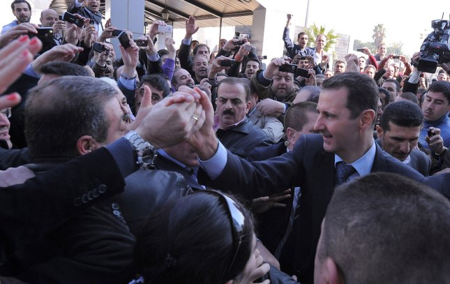 A handout picture released by the Syrian Arab News Agency (SANA) shows Syrian president Bashar al-Assad (R) shaking hands with his supporters upon his arrival to vote for the referendum on a new constitution, at a polling station, in Damascus, Syria, February, 26 2012. Syrians began voting on February 26 on a new constitution that the government says will introduce political pluralism. More than 14,000 polling stations opened nationwide for about 15 million eligible voters. The opposition announced a boycott of the referendum. UPI.