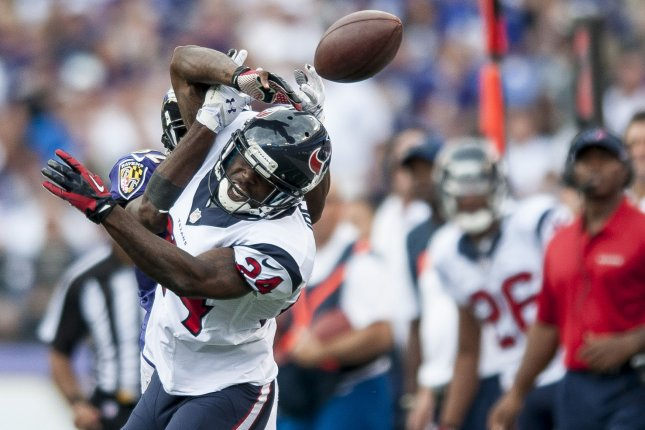 Former Baltimore Ravens wide receiver Torrey Smith battles for a pass with Houston Texans cornerback Johnathan Joseph during third-quarter action on September 22, 2013 at M&T Bank Stadium in Baltimore. File photo by Pete Marovich/UPI