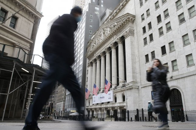 Pedestrians pass the New York Stock Exchange on Wall Street in New York City on January 27. Photo by John Angelillo/UPI