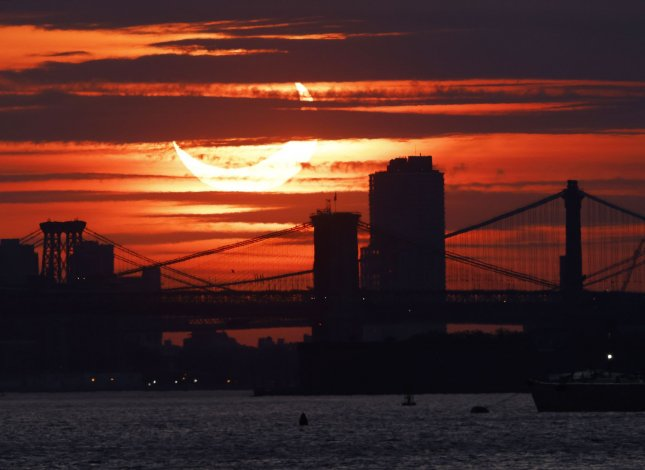 A partial solar eclipse rises behind the Brooklyn Bridge and other east river crossings in Manhattan from Bayonne, N.J. Photo by John Angelillo/UPI