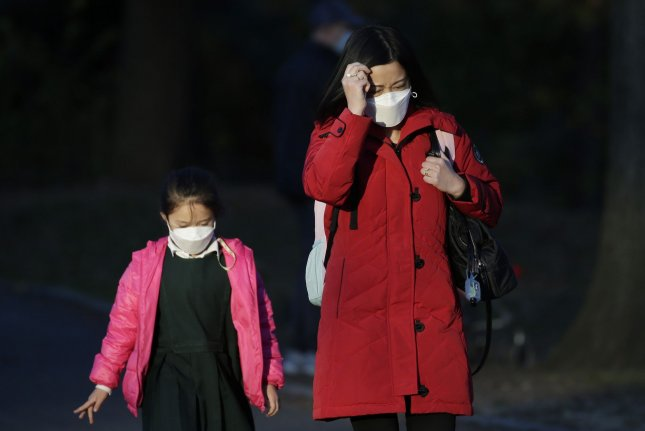 A woman and child wear face masks to prevent the spread of COVID-19 in Central Park in New York City in November 2020. File Photo by John Angelillo/UPI