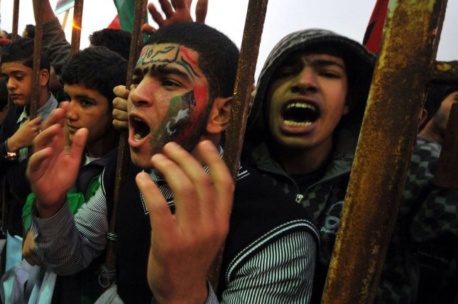 Protesters hold old national flags as they shout slogans against Libyan leader Moammar Gadhafi near the port of Benghazi, Libya along the Mediterranean coast on March 6, 2011. Loyal and rebel forces continue to battle for control of the country. UPI/Mohamaad Hosam