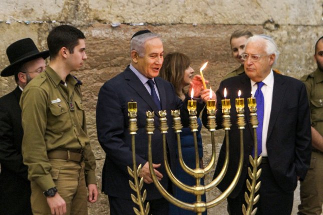 Israeli Prime Minister Benjamin Netanyahu (3rd-L) and U.S. Ambassador to Israel David Friedman (2nd-R) together light a candle during a menorah-lighting ceremony with Israeli soldiers for Hanukkah, the Jewish festival of lights, at the Western Wall in the Old City of Jerusalem on Thursday. Photo by Gil Cohen-Magen/UPI