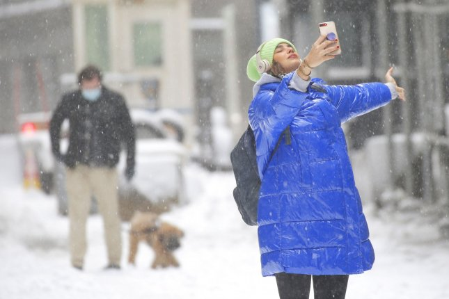 A girl reacts to falling snow during a snow storm on Wall Street in New York City on December 17. The city could receive some snowfall Friday. File Photo by John Angelillo/UPI