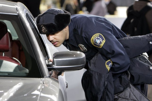 A Detroit police officer looks at a Dodge Charger. (File/UPI/Mark Cowan)