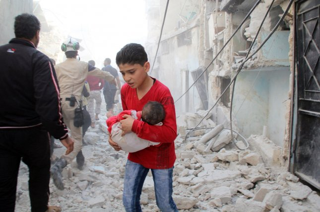 A Syrian boy carries an infant as he looks for his relatives in the rubble of destroyed houses following what local activists say was an airstrike by Russians in the rebel-held area of Kallasah, on the outskirts of Aleppo, Syria, in October, 2015. A cease-fire in the city has been announced by the United States after a recent uptick in violence there. File Photo by Ameer Alhalbi/UPI