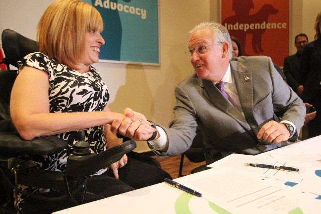 Missouri Gov. Jay Nixon shakes the hand of Aimee Wehmeier, President and CEO of Paraquad, after signing House Bill 1565 which makes it easier for Missourians who are elderly, blind or disabled to qualify for Medicaid on Thursday. Photo by Bill Greenblatt/UPI