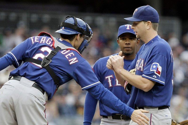 Texas Rangers starting pitcher Scott Feldman gets a tap from former catcher Taylor Teagarden. UPI/John Angelillo
