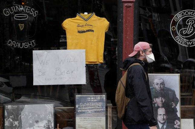 A man wears a protective mask while walking past a closed Bar in the Little Italy section of Manhattan in New York City on Tuesday. A few states are starting to let businesses reopen. Photo by John Angelillo/UPI