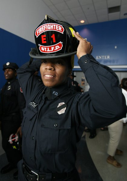 Cicely Tucker tries on her new helmet after being promoted to probationary firefighter for the St. Louis Fire Department in St. Louis on August 17, 2007. Tucker is the only women out of 17 recruits from the Cecil Morris Recruit Class to earn the promotion. (UPI Photo/Bill Greenblatt)