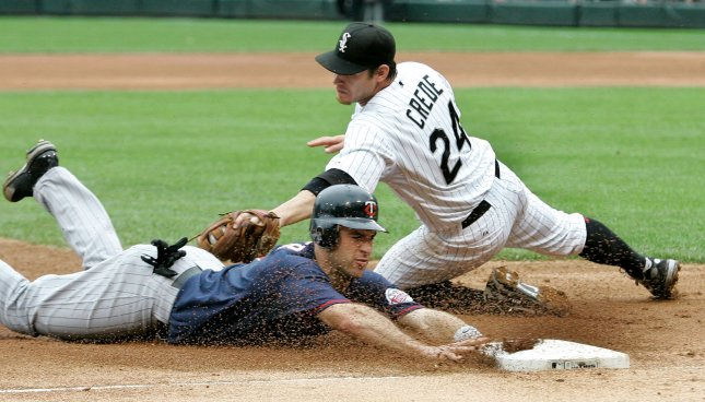 Minnesota Twins' Joe Mauer slides safely into third base, advancing from first on Justin Morneau's single as Chicago White Sox third baseman Joe Crede tries to make the tag during the fifth inning in Chicago on June 9, 2008. (UPI Photo/Brian Kersey)