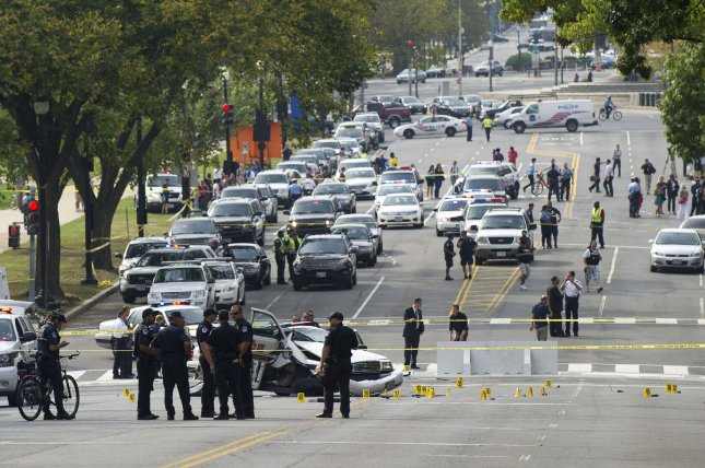 Police officers gather near the U.S. Capitol after a car chase from the White House Oct. 3, 2013. The woman who drove the vehicle being pursued was shot to death. A wrecked car is behind the officers. UPI/Kevin Dietsch