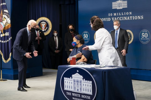 Before getting her COVID-19 vaccine, President Joe Biden talks with Linda Bussey, who has worked at a Safeway for 37 years, during a ceremony commemorating the 50 million vaccine doses given under the Biden administration at the White House on Thursday. Pool Photo by Doug Mills/UPI