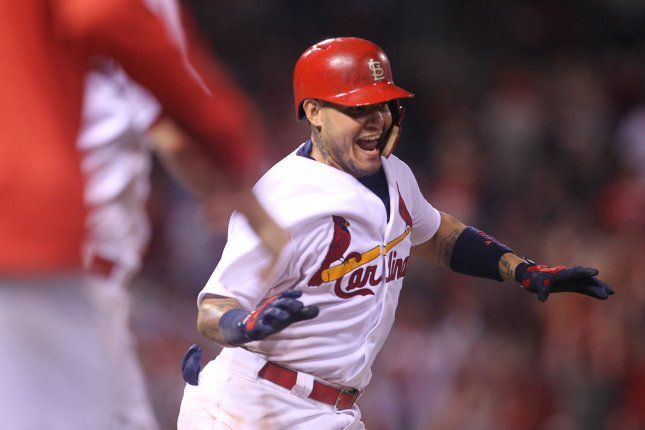 St. Louis Cardinals Yadier Molina tries to make it to first base before getting mobbed by teammates after getting hit by a pitch with bases loaded against the Cincinnati Reds in the ninth inning at Busch Stadium in St. Louis on August 8, 2016. St. Louis won the game 5-4. Photo by Bill Greenblatt/UPI