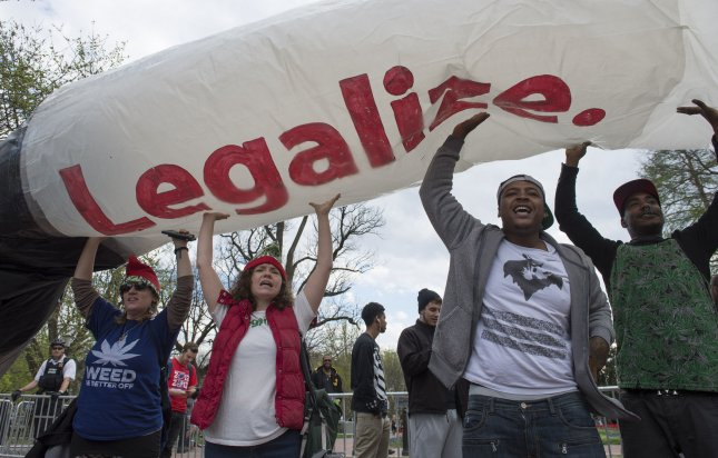 A group of pro-legalization marijuana supporters take part in a protest to urge President Barack Obama to stop marijuana arrests, pardon offenders and give greater access to medical marijuana and deschedule cannabis. On Saturday, Alaska opened its first legal pot shop, joining the ranks of Colorado, California and Oregon, who are raking in hundreds of millions of dollars on the sales. FIle Photo by Kevin Dietsch/UPI