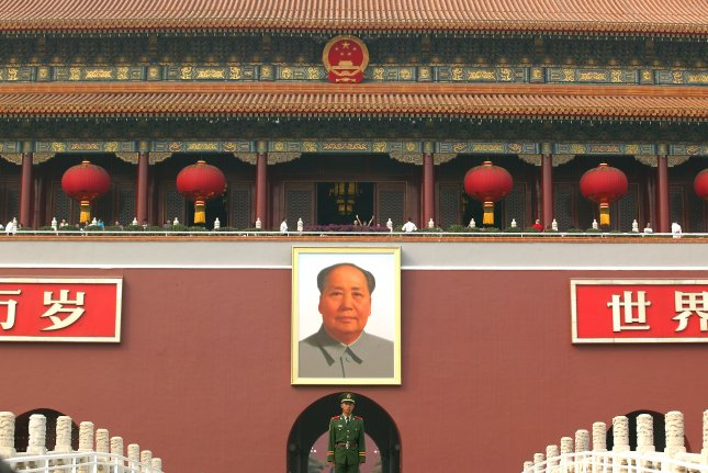 A Chinese soldier stands guard in front of a giant portrait of China's former helmsan Mao Zedong hanging in Tiananmen Square's north gate in Beijing on China's National Day, October 1, 2006. Mao's funeral was held in the square on September 18, 1976. File Photo by Stephen Shaver/UPI