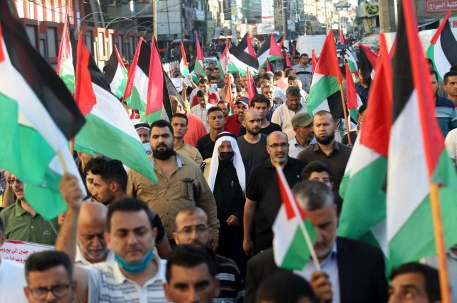 Palestinians lift national flags during a protest against an Israeli ultra nationalist flag march in Jerusalem's Old City in Rafah in Southern Gaza on Tuesday. The Israeli march celebrates the anniversary of Israel's 1967 occupation of Jerusalem's eastern sector. Photo by Ismael Mohamad/UPI