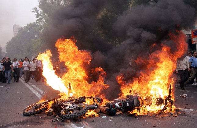 A motorcycle burns as supporters of reformist candidate Mir Hossein Mousavi gather on the streets to protest the results of the Iranian presidential election in Tehran, Iran on June 13, 2009. (UPI Photo)