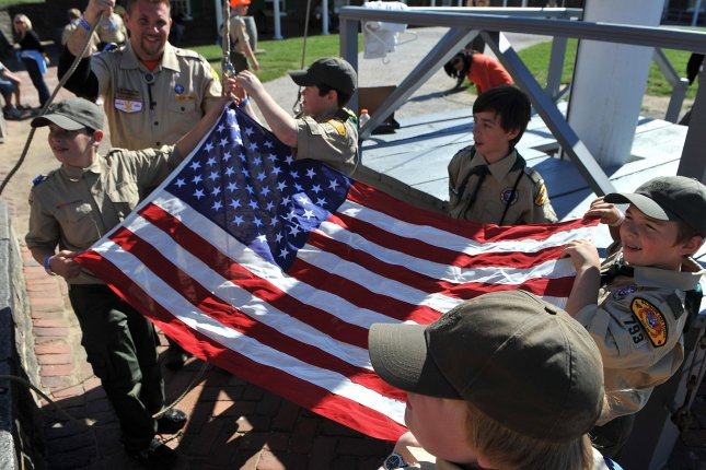 Boy Scouts fold a flag during a celebration of the 100th anniversary of the Boy Scouts of America in 2010. The organization is now considering ending its ban on gay troop leaders. File Photo by Kevin Dietsch/UPI