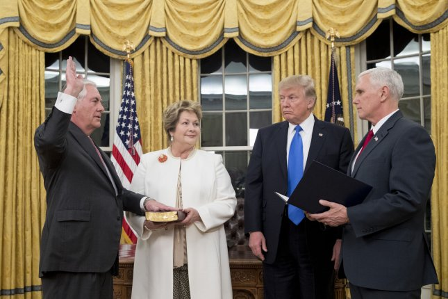 President Donald J. Trump watches as Rex Tillerson (L) is swornin as secretary of state by Vice President Mike Pence (R) beside Tillerson's wife, Renda St. Clair, in the Oval Office of the White House on Wednesday. Pool Photo by Michael Reynolds/UPI