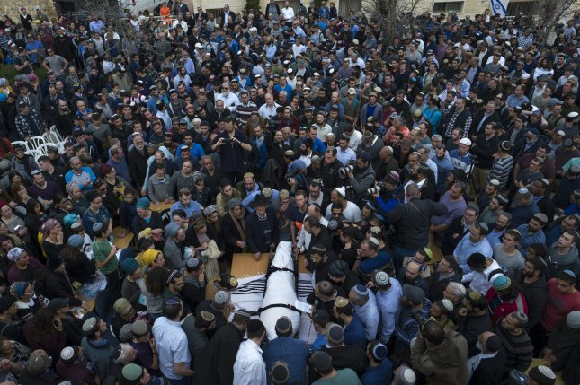 Family and friends surround the body of Rabbi Itamar Ben Gal at his funeral Tuesday in the West Bank settlement of Bracha. Ben Gal was stabbed to death Monday. Photo by Jim Hollander/UPI