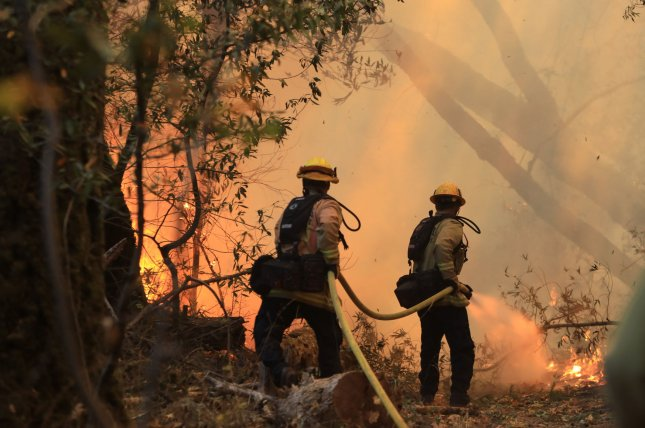 Firefighters battle the Nuns Fire in Santa Rosa, Calif., on Saturday The wildfires in the region could cost more than $3 billion, officials said. Photo by Khaled Sayed/UPI