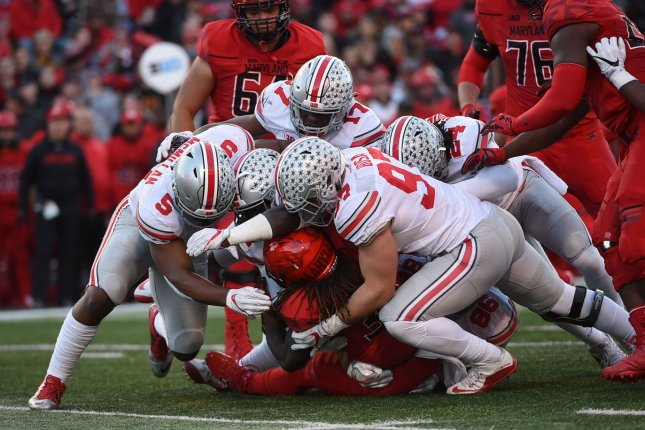Ohio State Buckeyes linebacker Raekwon McMillan (5), linebacker Jerome Baker (17) , Malik Hooker (24) and defensive end Nick Bosa (97) tackle Maryland Terrapins running back Kenneth Goins Jr. during a game in 2016. Photo by Molly Riley/UPI