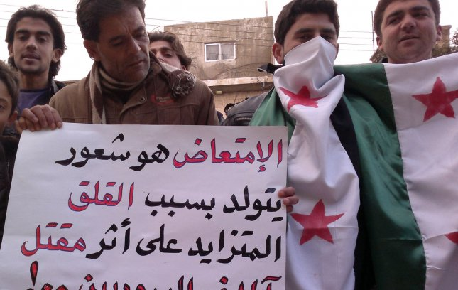 Syrian demonstrators hold up signs and Syrian independence flags during a protest against Syria's President Bashar al-Assad in Kafranbel, Syria, February 19, 2012. Syrian opposition called for civil disobedience in the capital Damascus, while Egypt recalled its ambassador to Damascus, state television said on Sunday, in what appeared to be the latest step in a series of Arab diplomatic moves to intensify pressure on President Bashar al-Assad, who is trying to crush a popular uprising in Syria. UPI