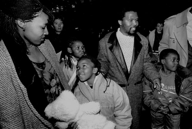 Princess Zenani Mandela Dlamini (L) daughter of South African civil rights activists Nelson and Winnie Mandela, arrives at Logan International Airport from Johannesburg, South Africa, with her three children January, 14 1988. Zamaswazi Dlamini (2nd L), 8, daughter; Zaziwe Dlamini (2nd L B), 10, daughter; Prince Thumbumuzi Dlamini (2nd R) her husband who greeted them, and Zinhle Dlamini ®, 7, son. Both parents are attending Boston University. (UPI PHOTO/Stu Cahill/FILES)