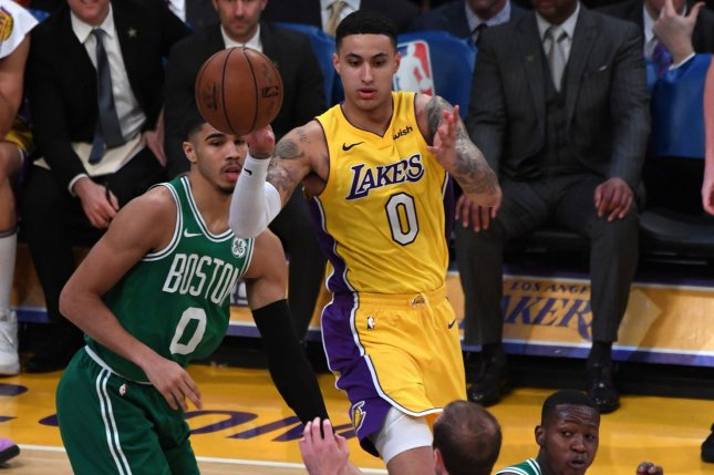 Los Angeles Lakers forward Kyle Kuzma (0) passes the ball to teammate Alex  Caruso (4) during a game against the Boston Celtics on January 23, ...