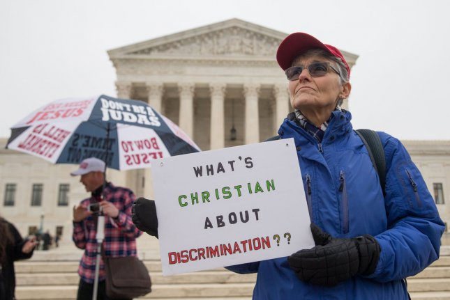 A protester holds a sign outside the U.S. Supreme Court on December 5 in the case of Masterpiece Cakeshop v. Colorado Civil Rights Commission. The court ruled Monday that Colorado baker Jack Phillips can legally decline, on religious grounds, to provide services to same-sex couples. File Photo by Erin Schaff/UPI