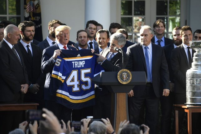 President Donald Trump holds up a hockey uniform presented by St. Louis Blues National Hockey League principal owner Tom Stillman. Photo by Mike Theiler/UPI
