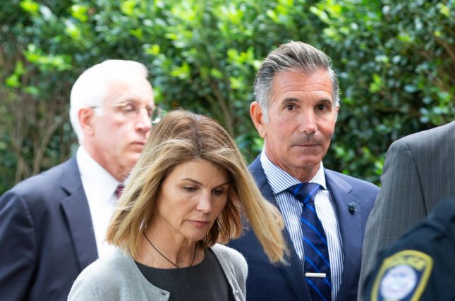 Actress Lori Loughlin (L) and her husband, fashion designer Mossimo Giannulli, exit the U.S. courthouse in Boston last year. They were sentenced to prison on Friday in a college admissions scandal. File Photo by Matthew Healey/UPI