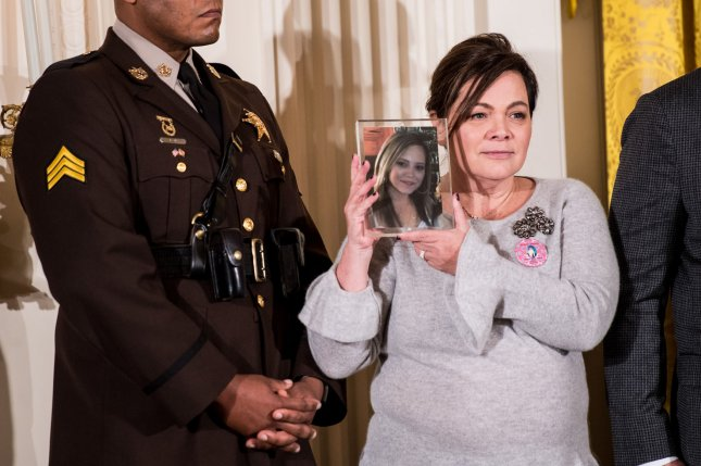A woman holds a photo of a loved one lost to the opioid epidemic as President Donald Trump labeled the opioid crisis a public health emergency in October. File Photo by Kevin Dietsch/UPI