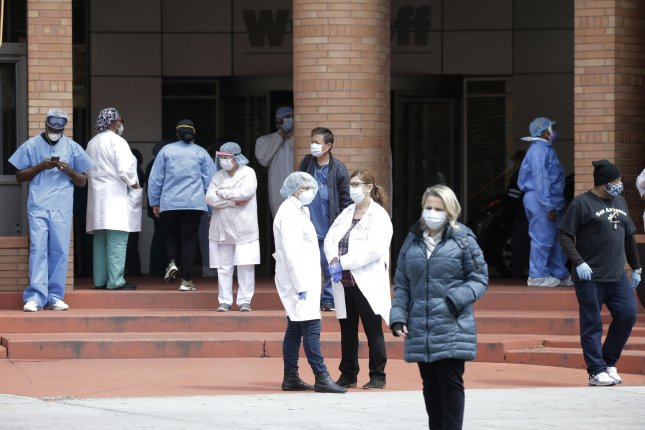Healthcare workers wearing protective face masks and medical clothing stand outside an entrance to Wyckoff Heights Medical Center in New York City in April. Photo by John Angelillo/UPI