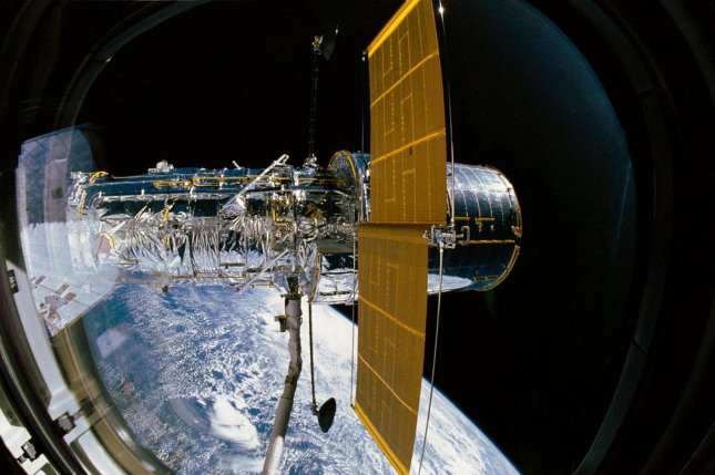 On April 25, 1990, the Hubble Space Telescope was deployed from the cargo bay of space shuttle Discovery. Hubble, pictured here during its release, has one of its two solar array panels deployed while still in the grasp of Discovery's remote manipulator system. NASA/UPI