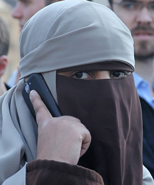 A woman wears a burqa (full-face veil) in front of Notre Dame Cathedral in defiance of a new French law banning the garment in Paris on April 11, 2011. The controversial new law takes effect today and officially bans all garments which cover the face. Violators are subject to a fine of 150 euros ($217). UPI/David Silpa