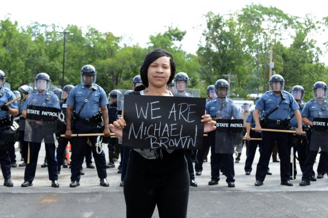 Arianna Whiteside leads demonstrators as they confront a wall of police during a protest march to the Ferguson Police Department in Ferguson, Missouri on August 11, 2014. People are upset because of the Ferguson Police shooting and death of an unarmed black teenager Michael Brown on August 9, 2014. 20 businesses sustained damage after a candlelight vigil turned violent with arsons, lootings and vandallism. UPI/David Broome