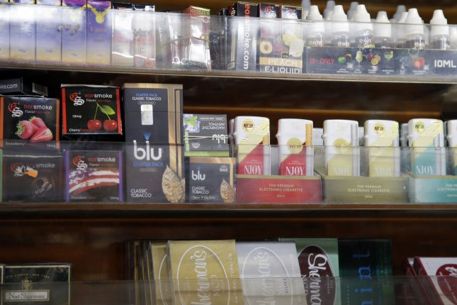 E-cigarettes and e-cigarette liquids on display at a New York City smoke shop. The FDA on Tuesday warned several companies against using kid friendly marketing to sell nicotine liquids for e-cigarettes. File Photo by John Angelillo/UPI