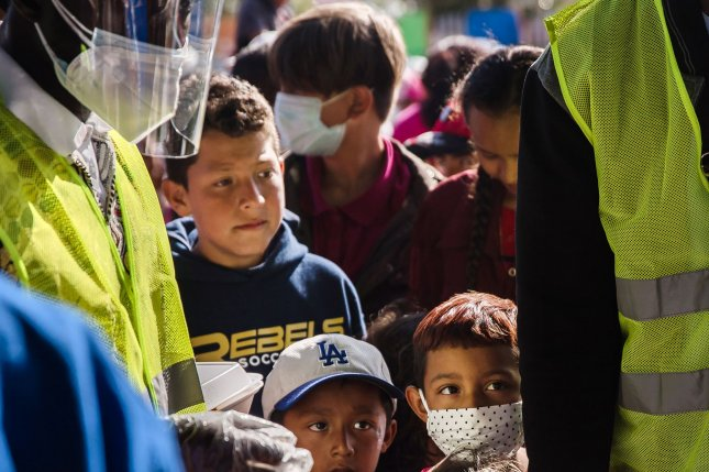 Children wait in line for food near El Chaparral plaza in Tijuana, Mexico on March 21. File Photo by Ariana Drehsler/UPI